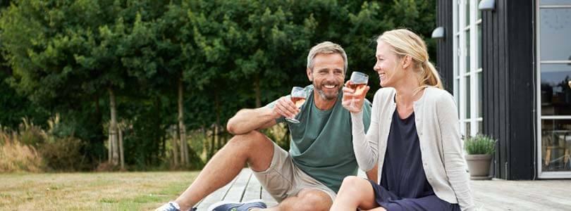 Ehepaar trinken wein am Ferienhaus in Bogense